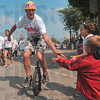 Tribune-Star/Joseph C. Garza<br /> Parade participation: Conner Hamilton, 5, high-fives a Greg Ewing supporting unicyclist during the Labor Day Parade Monday on Fourth Street.