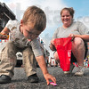 Tribune-Star/Joseph C. Garza<br /> Labor of love: Two-year-old Mathayus McCloud reaches for a package of candy recently tossed by the Terre Haute Fire Department as his mother, Casey Clifton, right, keeps an eye on him on Wabash Avenue Monday during the Labor Day Parade.
