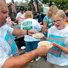 Tribune-Star/Joseph C. Garza<br /> For me?: Jerry DeLisle hands Charlene Loudermilk two bowls of hot beans during the bean dinner after the Labor Day Parade Monday at Fairbanks Park.