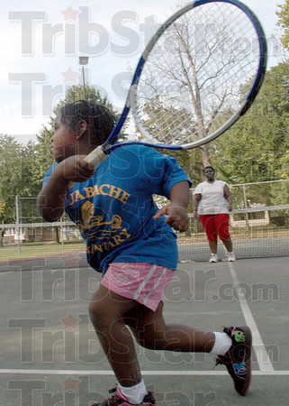 Swing: Six-year-old Kayleiss Hutchinson swings at a tennis ball thrown by Kanole Bagandi Tuesday afternoon at Collett Park.