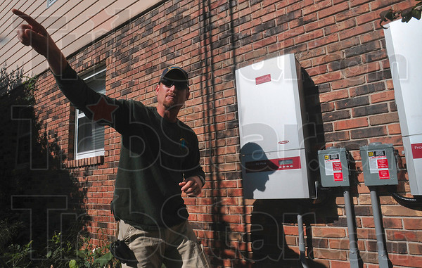 Tribune-Star/Joseph C. Garza<br /> DC to AC: Phillip Roberts, president of One Planet Solar, describes how energy created by a solar panel array on a barn roof is changed from DC current to AC current by inverters on the side of Dr. Harold and Terri Loveall's home Tuesday after the system was turned on earlier in the day.