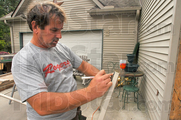 Measure twice: Harold Eversole, employee of Rogers Home Improvement, marks vinyl siding for cutting. The company is rebuilding a home that suffered severe fire damage.