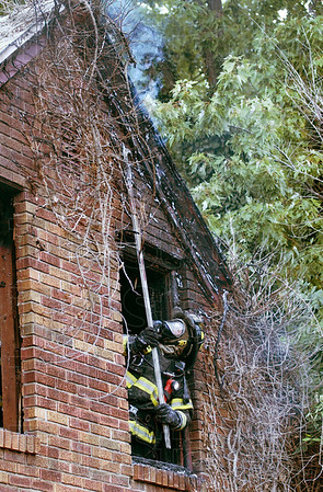 Detail work: Terre Haute firefighter Kyle Pettijohn uses a pike pole to pull burning soffit from a house on 7th street just south of Margaret Avenue Wednesday afternoon.