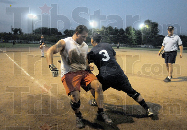 Safe: Terre Haute firefighter Butch Auler scores during game action Tuesday evening. Police catcher Josh Pirtle waits for the incoming throw.