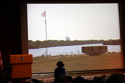 Before the briefing begins, a live camera shows the Press Site -- Clock and Flag Pole, with the countdown clock holding at T minus 3 hours and Space Shuttle Atlantis on Launch Pad 39-A in the background