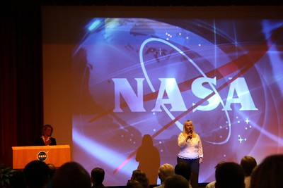 A NASA employee leads the The Star-Spangled Banner.  KSC Chief Financial Officer Susan Kroskey is at the podium.