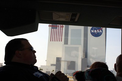 Chris, with the Vehicle Assembly Building in the background.  Each stripe on the flag is wide enough to fit the bus.