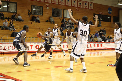 Newburgh Free Academy's Raymar Davis (#25) drives past Poughkeepsie's Dayron Whitaker (#2), Malik Dennard (#33) and Nate Gause (#30) during the game on Saturday, January 10, 2009 at Marist College in Poughkeepsie, NY. Poughkeepsie defeated NFA 74-70.