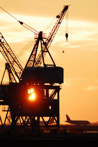 Sunrise through the cranes of the former General Ship Repair in Boston.