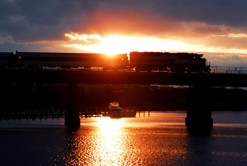An inbound Haverhill Line Train crosses the Mystic River at sunset with an April sky.