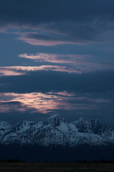 The moon rises over Goat Rocks on a slightly cloudy evening.