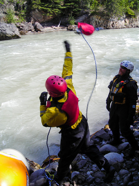 A rescuer tosses a throwbag across the channel to set up a crossing line.