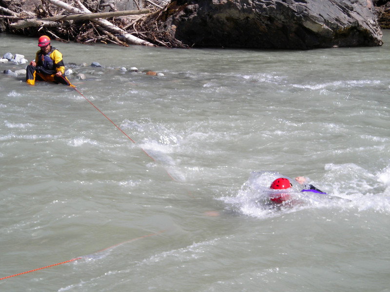 Ripping currents threaten to pull the rescuer off his crossing line and take him downstream.