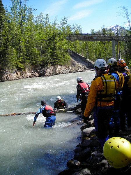 "A large log is moved into position in the current to simulate a ""strainer"", an obstruction of some sort that presents the danger of snagging a swimmer and pushing them under.."