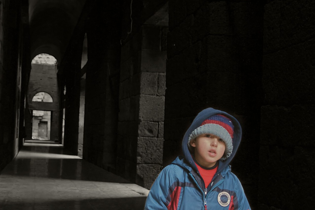 Hadi peering out of a corridor at the Roman amphitheatre at Bosra.
