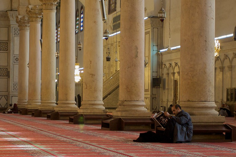 A man apparently oblivious to the bustle of people around him as he reads his newspaper at the base of the enormous columns inside the main prayer-hall in the Umayyad Mosque in Damascus.