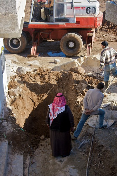 Way down in the hole (part 2): Ibrahim's father peering down into the newly-dug hole which he returned home to find at the entrance to his house.
