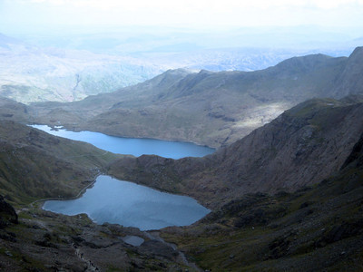 Summit 1, Mt Snowdon, Wales: Snowdon ascent. Haunted lakes: legend has it that King Arthur was taken away by the Ladies of the Lake here upon his death, and that his knights lie sleeping in a cave hereabouts, awaiting the horn call to rouse them once more to the defence of the realm. We looked for but did not see the knights. Evidence of faery presence, however, was abundant.