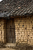 A rustic door and mud brick walls topped with ceramic shingles keep the weather out of this small shack.
