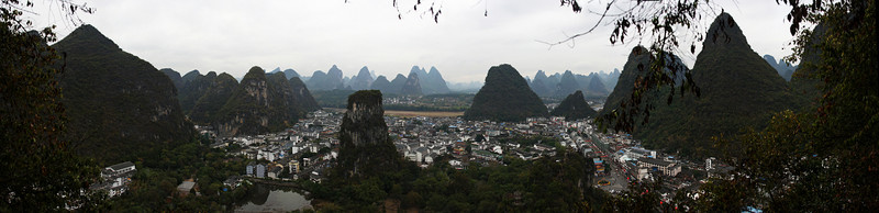 Downtown Yangshuo stretches away to the Li River, with a light rain diminishing the perpetual smog and opening up a view to a horizon filled with massive limestone towers.
