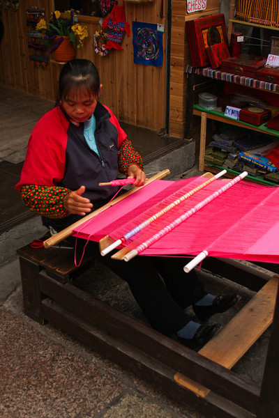 A local weaver works a loom to produce some brightly colored fabric, soon to add to the shelves of her shop in the tourist area of Yangshuo.