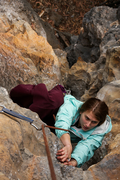Tracy pulls through an overhanging roof on a 5.8 at the Swiss Cheese Wall.