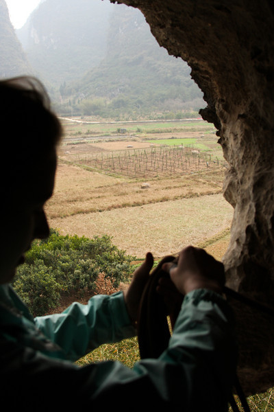 The beautiful scenery of China's farmland falls away as Tracy coils the rope in preparation for a rappel.