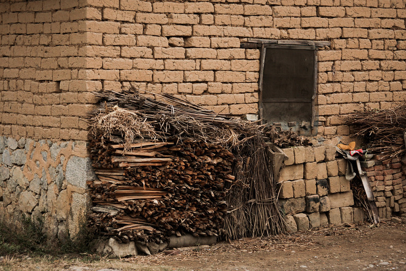 Firewood sits stacked against the mud brick walls of a local residence.