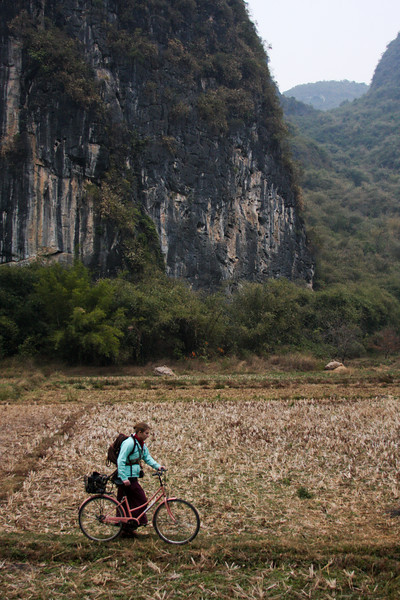 Access to the Swiss Cheese Wall in Yangshuo lies across a farmer's rice field, a bit barren and dry at this time of year.