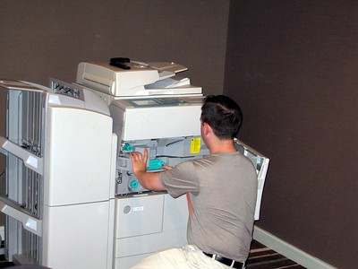 Convention Board Member Rocky Fernandez negotiates with the copier in the convention office