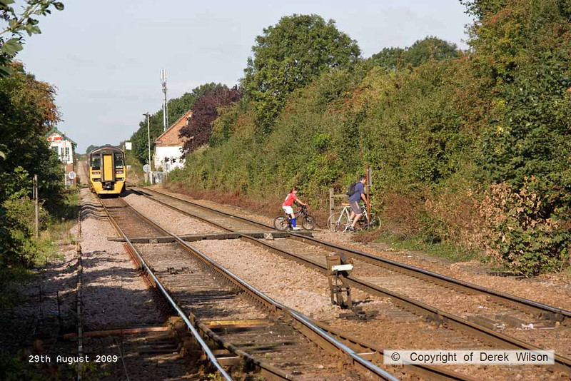 090829-006     With class 158 no. 158799 still waiting for right of way, two cyclists, with their view blocked by the unit, ride over the foot crossing. If they had been about thirty seconds later, they would had a rather close shave with a Freightliner intermodal which was speeding towards them, out of sight behind the unit. Will people never learn!! See the next image.