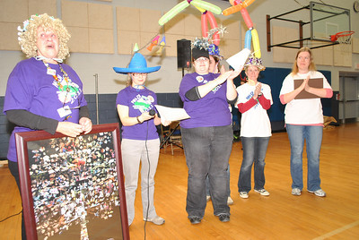 Marj Allen reacts to the overwhelming applause of over 1,500 people at Nashua High School North at NH Destination ImagiNation State Finals, as she is recognized for 30 years of service to the non-profit educational program. A few of her former team members react.