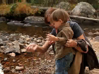 Nika shows Luke how to throw rocks into the river