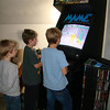Andrew and Tommy playing a game on the arcade in the man cave while Aidan watches
