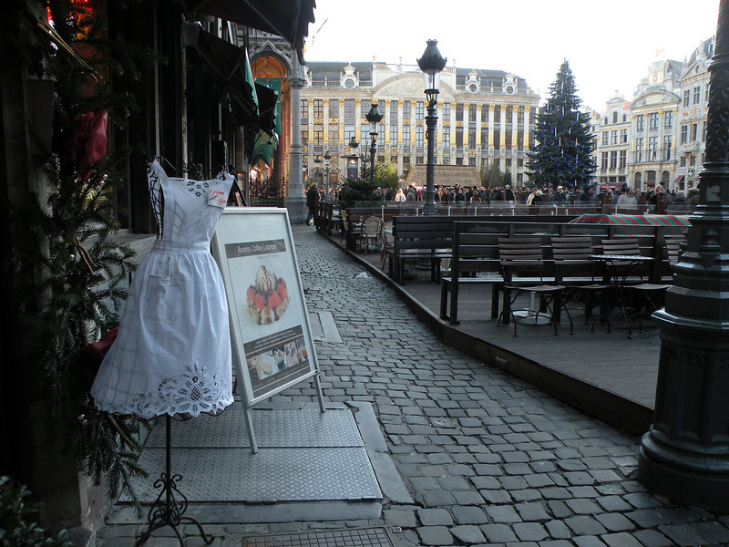 an apron clad manequin in front of a lace shop before Belgium's town square