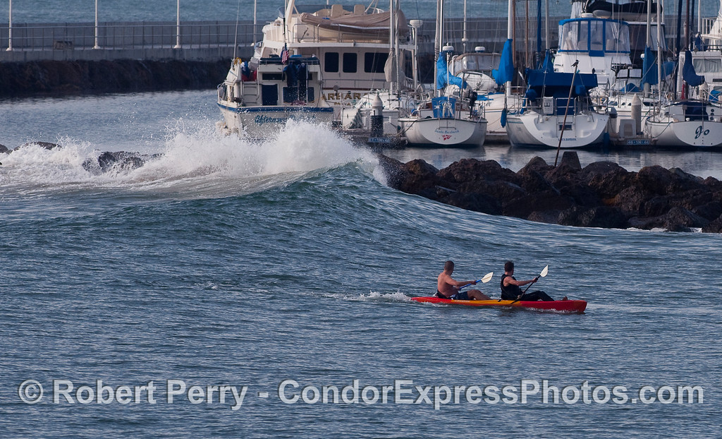 Two kayakers look on as a big swell and a high tide push water over the top of the Santa Barbara Harbor breakwater.