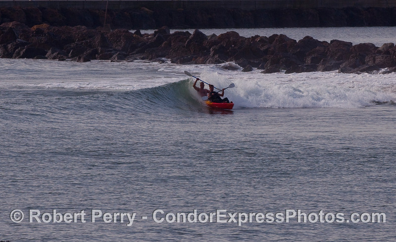 Two kayakers enjoy a wave at the sandspit, Santa Barbara Harbor.