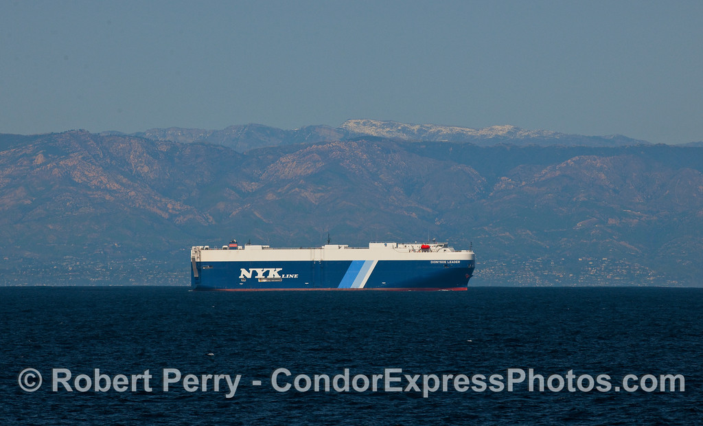 "The car-carrying ship ""Dionysos Leader"" heads eastward past snow capped peaks en route to Port Hueneme."