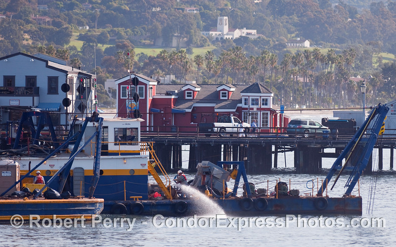"The Santa Barbara Harbor dredge barge ""La Encina"" at work.  Stearn's Wharf can be seen in the background."