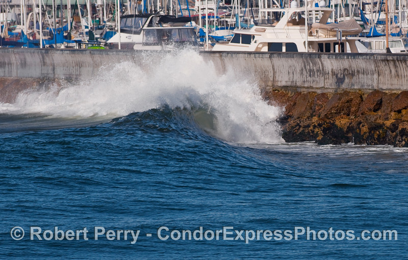 A wave breaks along the rocks below the breakwater, Santa Barbara Harbor.