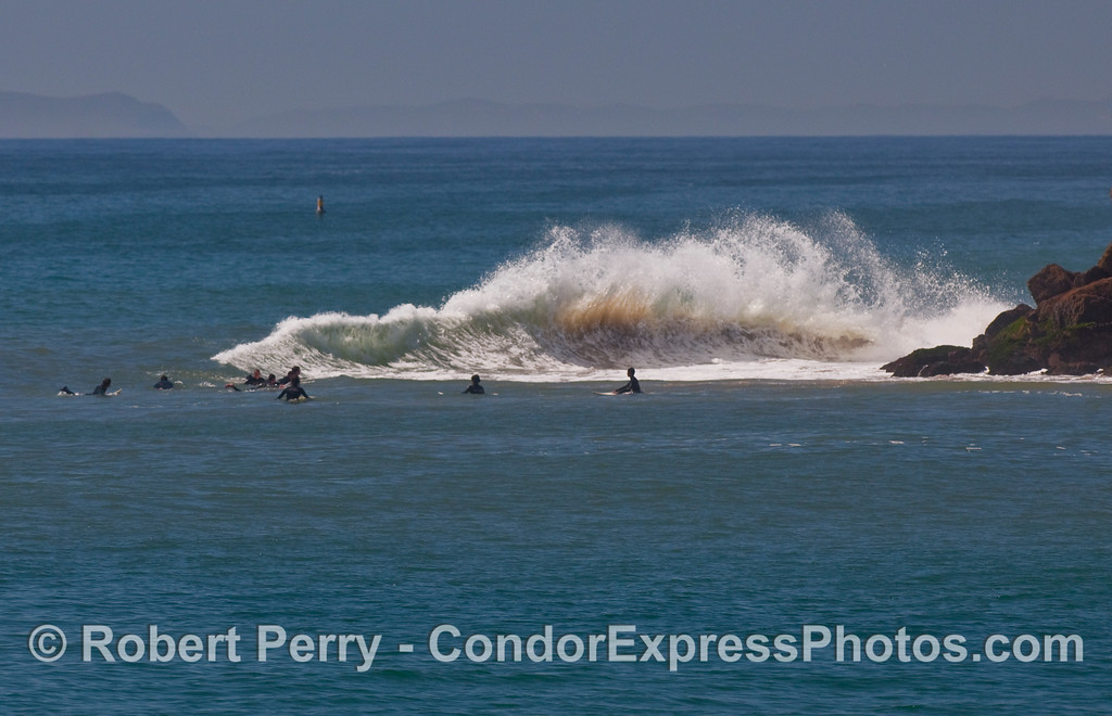 Surfers wait for waves to wrap around the jetty at Santa Barbara Harbor.