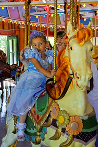 Amelia riding the carousel at her birthday party