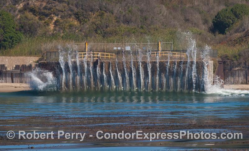 A wave slams against the seawall protecting a Venoco oil well on Elwood beach.