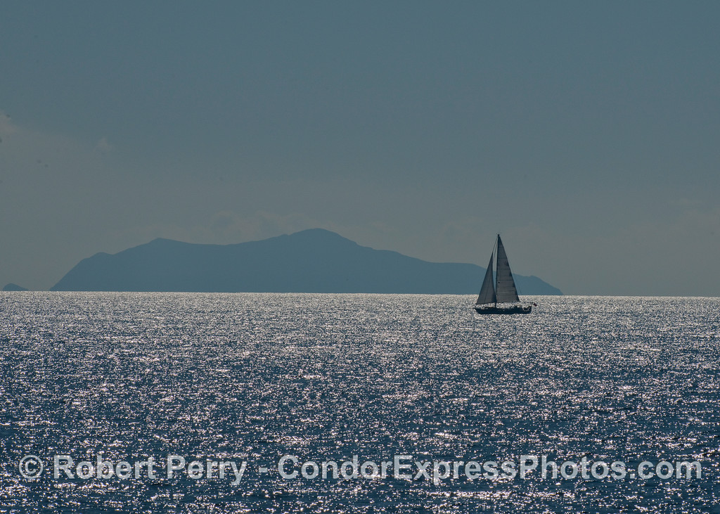 A lone sailboat on a sparkling sea with West Anacapa Island in the background.