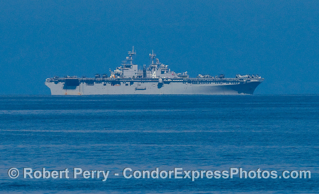 US Navy warship #4 with a flight deck full of helicopters and jet aircraft on maneuvers in the Channel.
