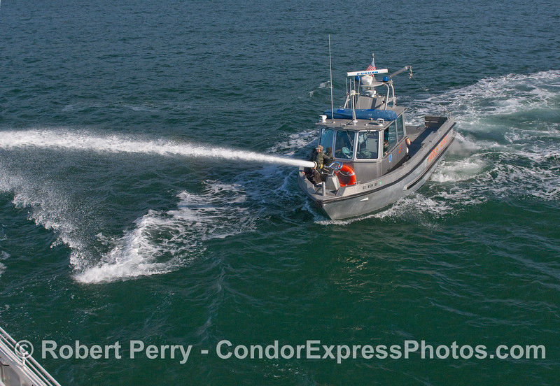 A Santa Barbara Harbor Patrol boat shoots its fire nozzle as a demonstration for the passengers on board the Condor Express.