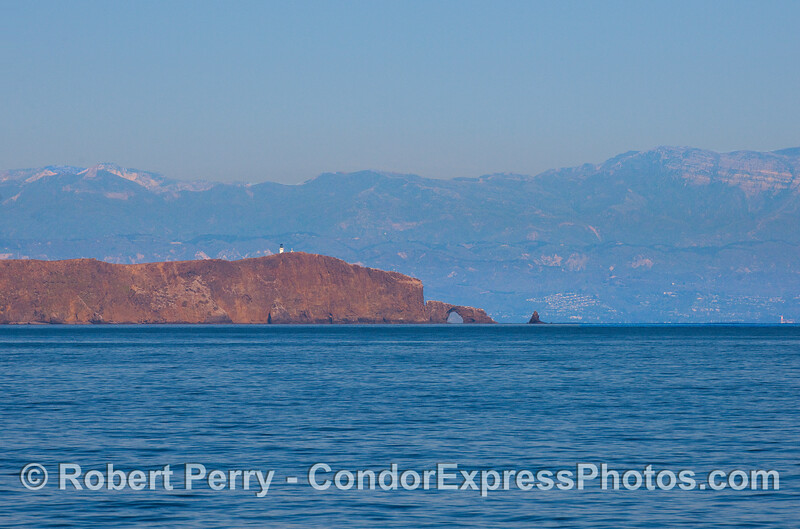 The southern face of East Anacapa Island and Arch Rock with the Santa Ynez mountains in the background.