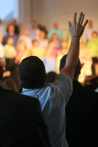 Church member Paul Lowry raises a hand in worship during Easter services at Western Avenue Baptist Church in Statesville, NC.