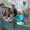 Lots to offer: Janet Svoboda looks over some of the shopping bags offered by Kim Doti and the Union Hospital Gift Shop at their table in the lower lobby Thursday afternoon. Several businesses and organizations presented their wares and services at the Earth Day event.