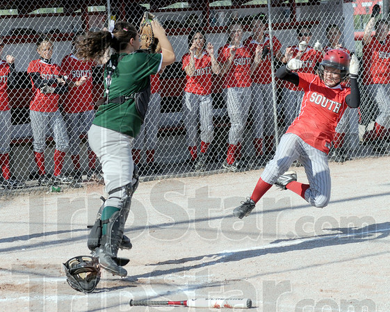 Scoring leap: South's #16, Rebecca Latta starts her slide into home plate as North Central's #6, Lainey Thompson catches the incoming throw. Latta was called safe on the play.